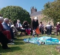 Group sitting in a circle in the quiet garden at Paul Church, Penzance