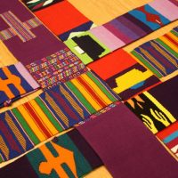 Multi coloured fabrics from around the world form a cross