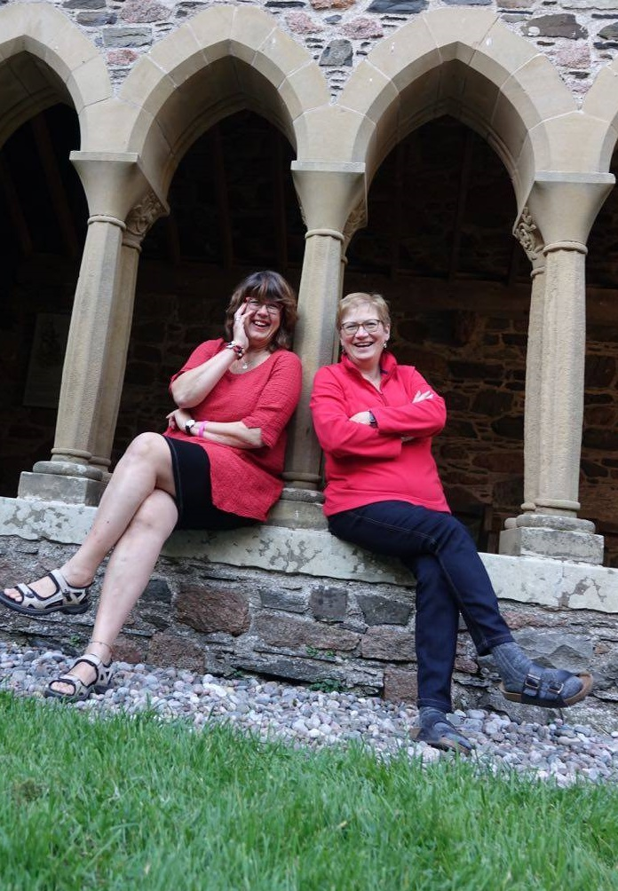 Pat Bennett and Alison Adam sitting in the cloisters in Iona Abbey